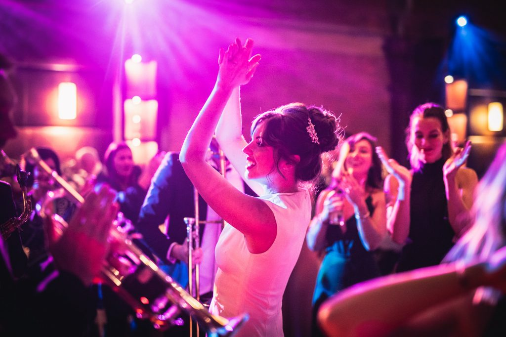 Guide To Booking Music For Your Wedding - A bride dances whilst a trumpeter plays