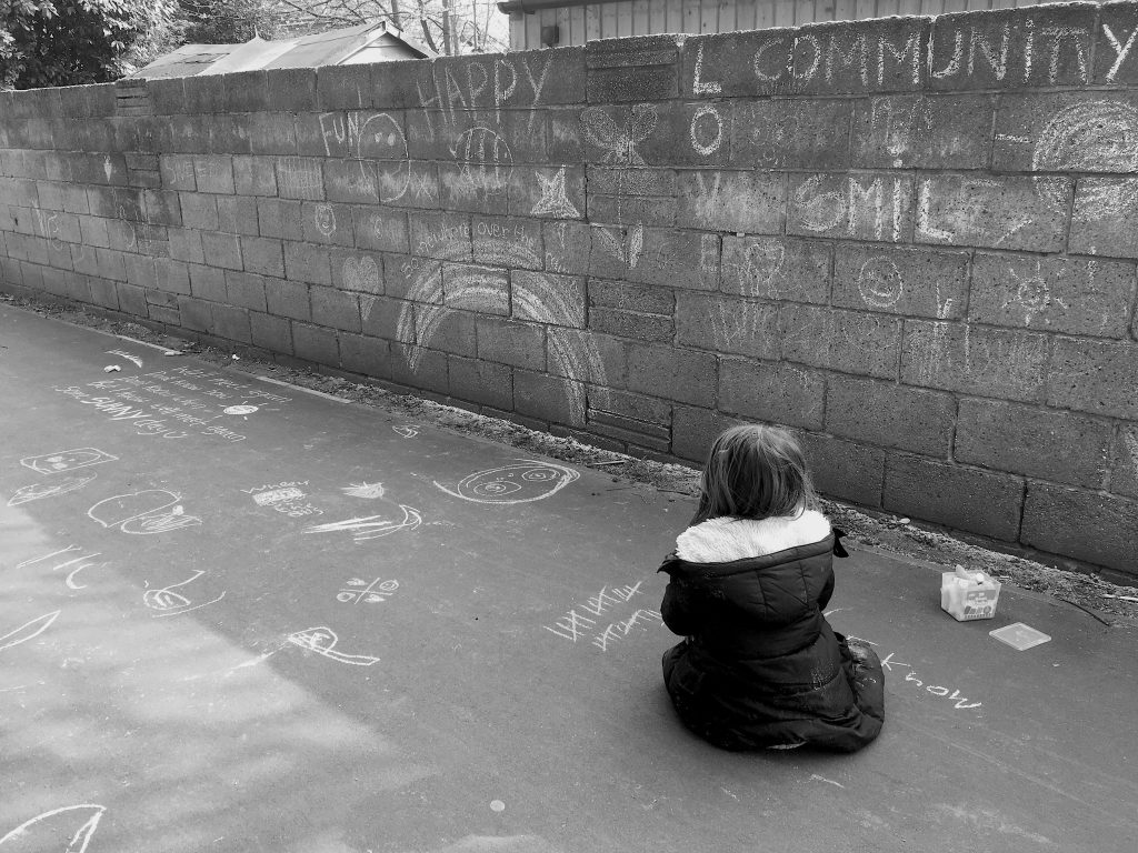 One year on. Child sat down looking at a wall illustrated with chalk writing and drawings.